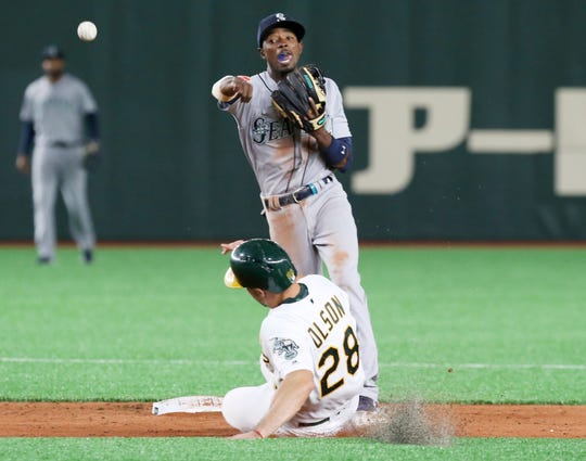 Seattle Mariners second baseman Dee Gordon throws to first as Oakland Athletics' Matt Olson is forced out in the eighth inning of Game 1 of their Major League opening series baseball game at Tokyo Dome in Tokyo, Wednesday, March 20, 2019.