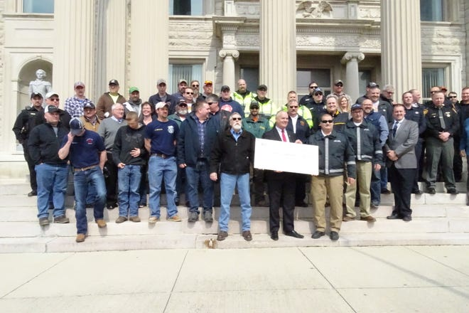 State Fire Marshal Jeff Hussey stands with firefighters and community leaders from across the county on the Crawford County Courthhouse steps Wednesday as he awards a grant for new MARCS radio equipment.