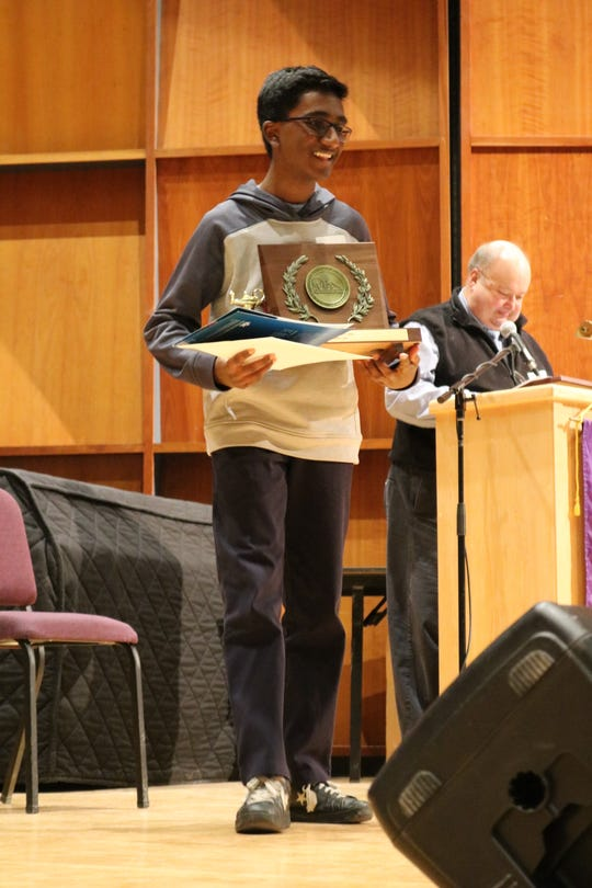 State spelling champion Raghav Dhandi, an 8th-grade student at Montpelier's Main Street School, hold his prize at the Vermont Scripps Spelling Bee at St. Michael's College on March 19, 2019.
