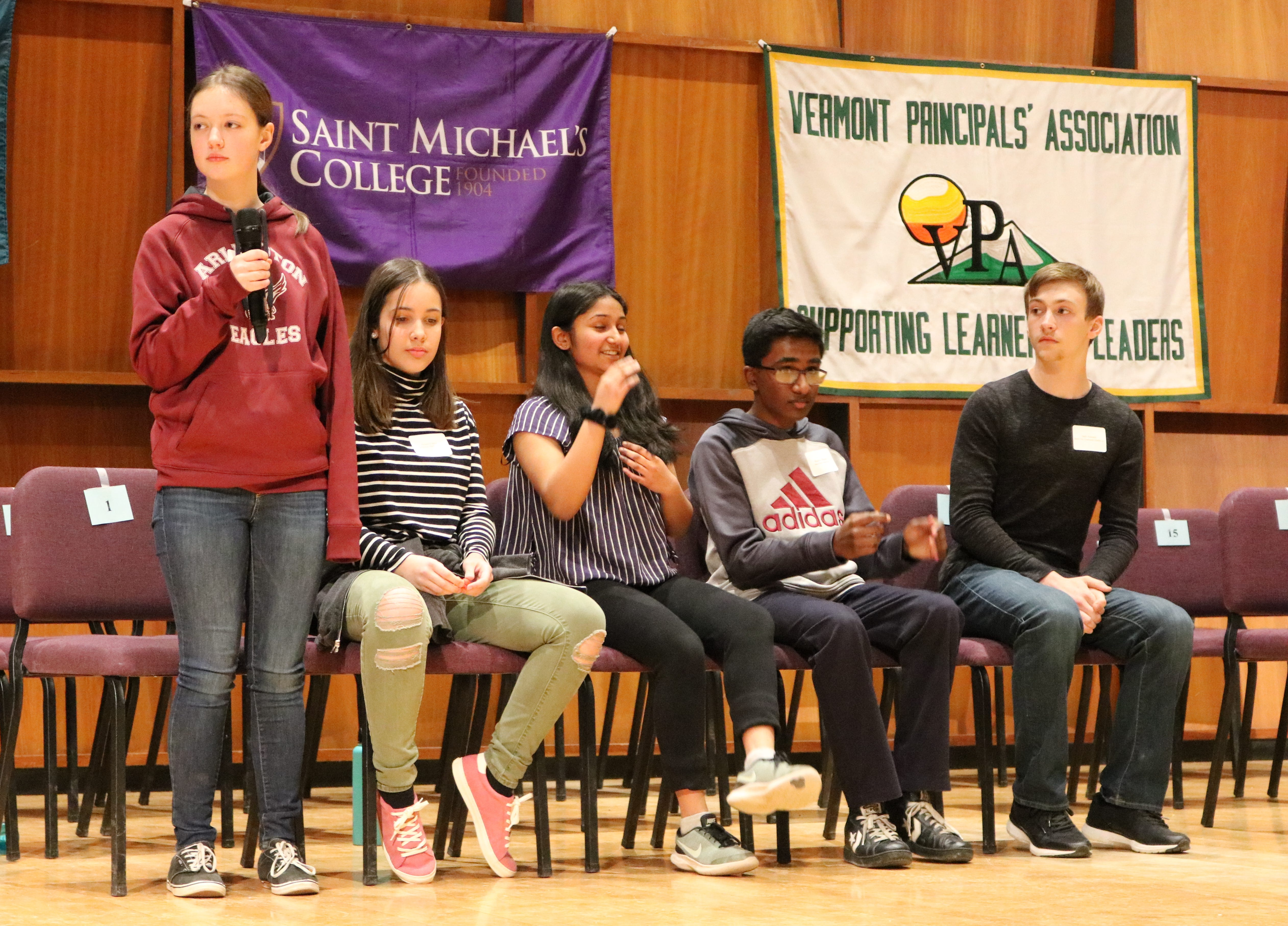 The final five sit together at the Vermont Scripps Spelling Bee at St. Michael's College on March 19, 2019. From left to right are: Audrey Robinson of Arlington Memorial, Grace Casey of Crossett Brook Middle School, Tanmaye Nazre of F. H. Tuttle Middle School, Raghav Dhandi of Main Street School, and Seth Almand of Barre City Middle School.