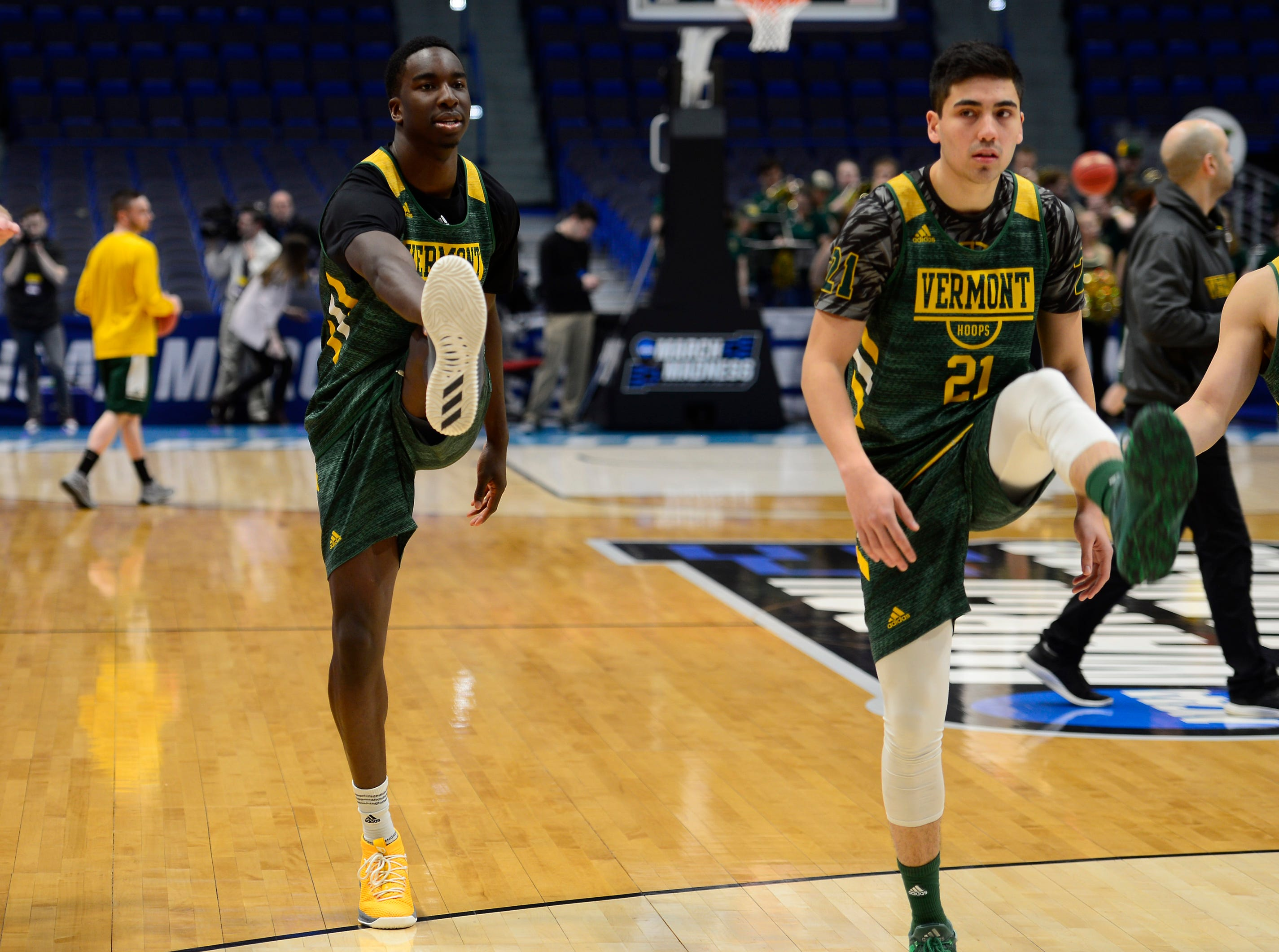 Vermont's Ra Kpedi, left, and Everett Duncan stretch before practice Wednesday at the XL Center in Hartford, Connecticut.