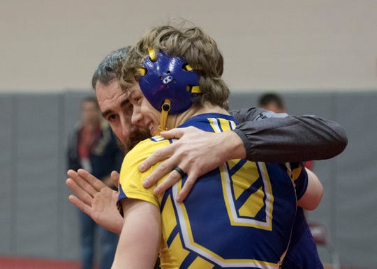 Unioto senior Ashten Moody hugs Unioto wrestling coach Adam Dettwiller after celebrating his 100 win after wrestling Zane Trace's Alex Brown during the annual Vinton County Tournament in December of 2018.