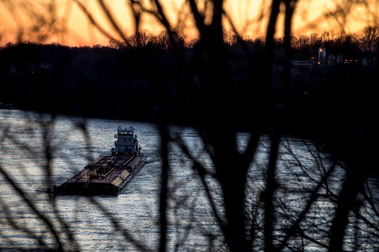 A barge moves steadily upstream against the current on the Cumberland River, which until recently was inundated by flood waters at Kings Bluff in Clarksville, Tenn., on Saturday, March 16, 2019.