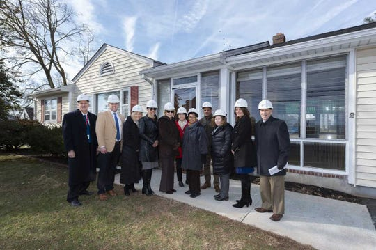 Robert Wood Johnson University Hospital Somerset SHELTER Task Force members gathered earlier this year to commemorate the start of the first Healing Homes renovation project.  This home will be completed and ready for occupancy in early April.  (left to right)  Joe Troegner, Director of Plant Operations; Patrick Delaney, Vice President of Operations; Barbara Mintz, Senior Vice President, Healthy Living and Community Engagement for RWJBarnabas Health; Deanna Minus-Vincent, Assistant Vice President, Social Impact & Community Investment for RWJBarnabas Health; Jan Holmstrup, Executive Director of Raritan Valley Habitat for Humanity; Maria Cermenaro, Administrative Assistant Community Health; Sarah Murchinson, Human Services Coordinator of Somerset County Human Services; Jean Benoit, social worker and program coordinator Healing Homes; Sharon Clark, Executive Director of Central Jersey Housing Resource Center; Serena Collado, Director of Community Health; and Tony Cava, President and Chief Executive Officer for RWJUH Somerset.