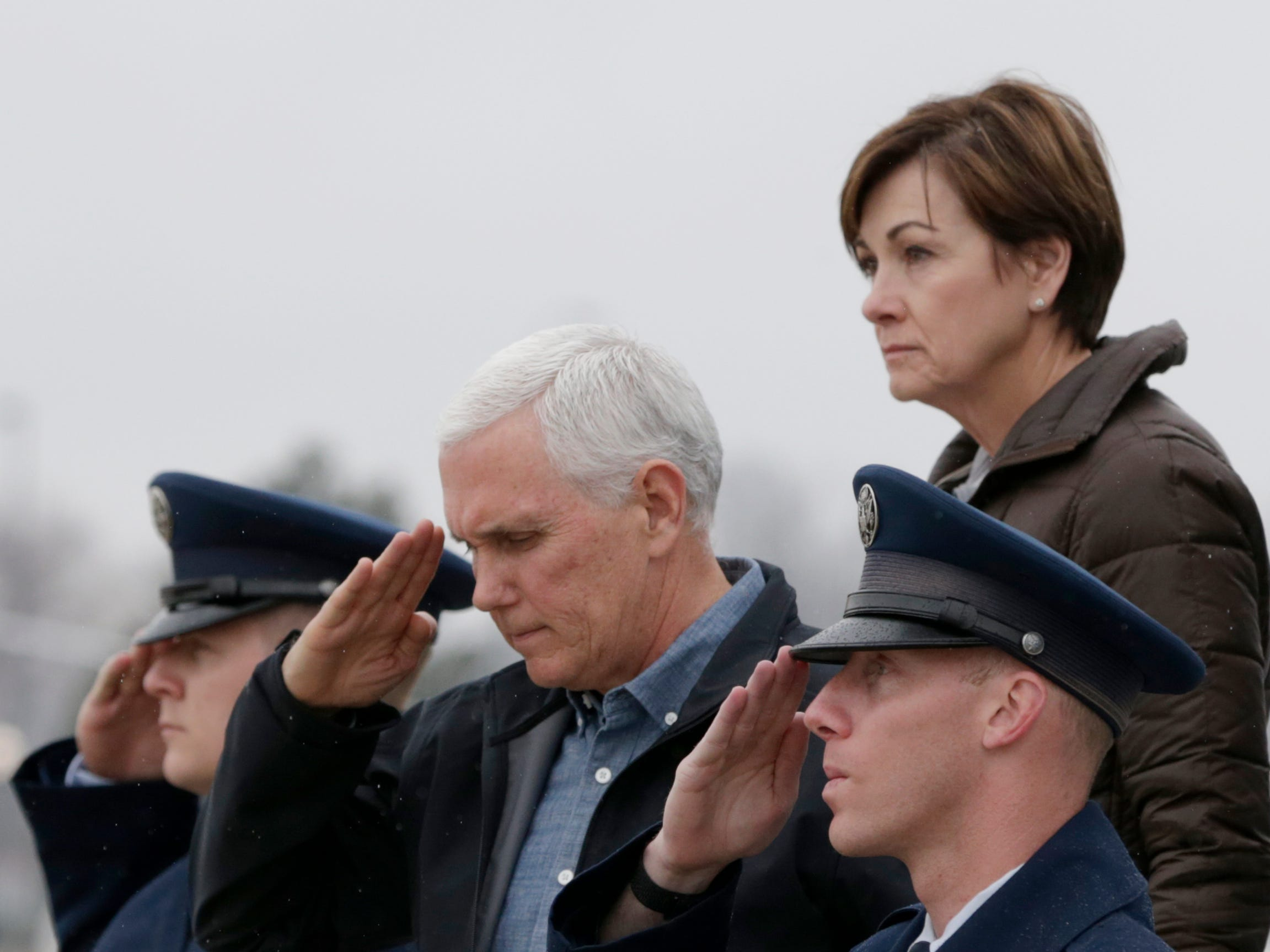Vice President Mike Pence salutes, as he is followed by Iowa Gov. Kim Reynolds upon his arrival in Omaha, Neb., Tuesday, March 19, 2019 to view the recent floods and offer support for it's victims.