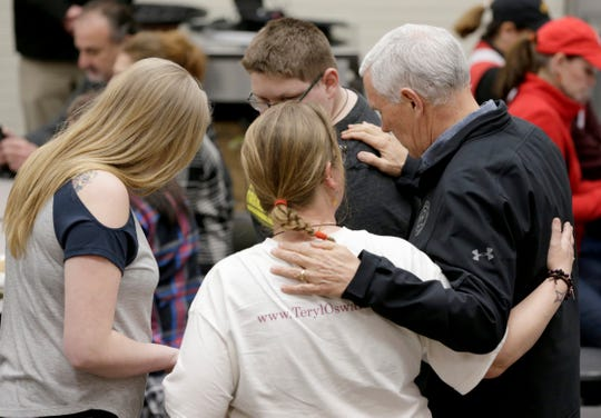 Vice President Mike Pence, right, prays with members of a family from Fremont, Neb., who were displaced by recent floods at a shelter in Elkhorn Middle School in Omaha, Neb., on March 19, 2019.