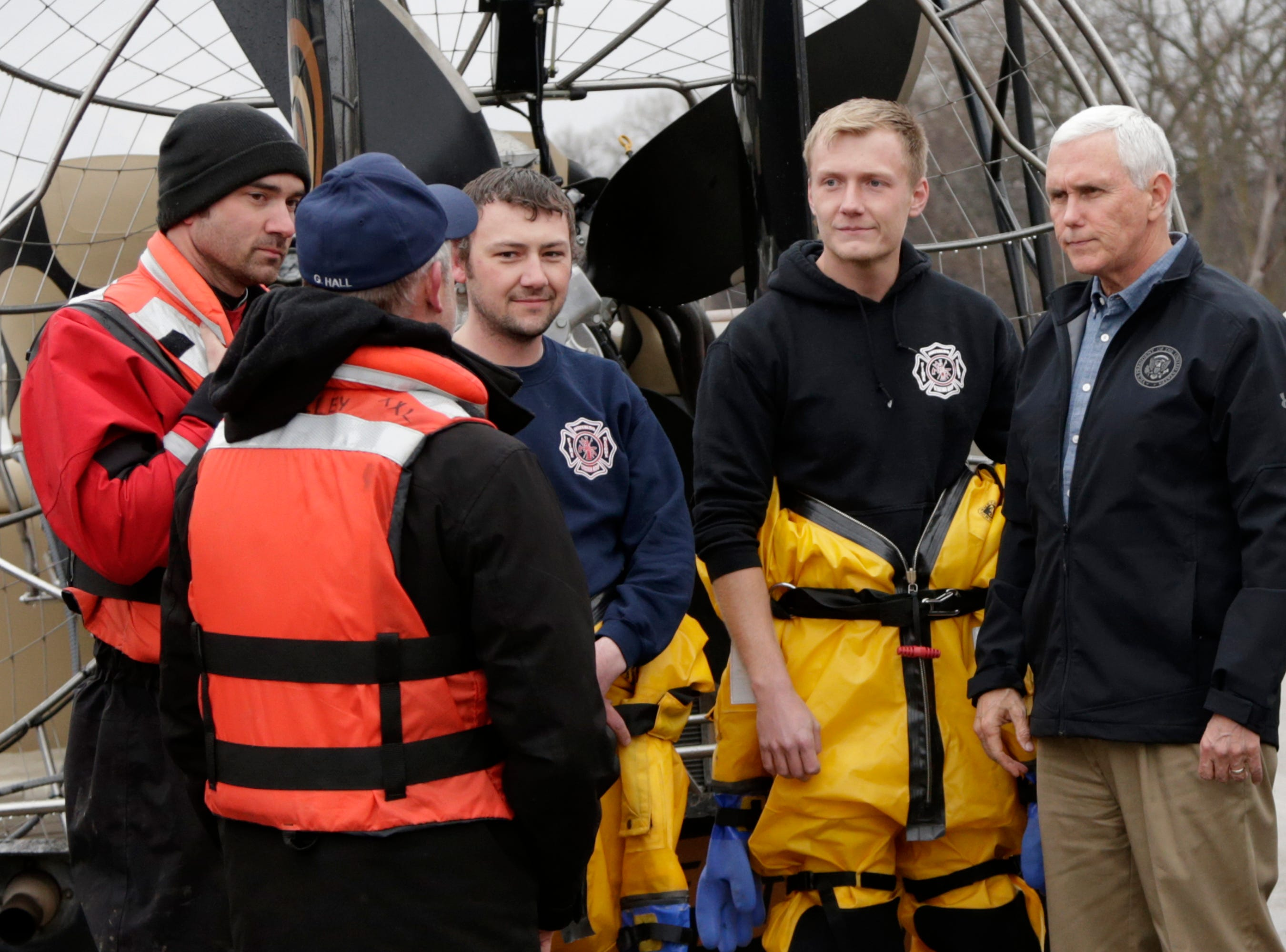Vice President Mike Pence, right, meets with first responders and volunteers who had helped evacuate people to safety during the recent floods, as the Elkhorn River is in the rear, in Omaha, Neb., Tuesday, March 19, 2019.