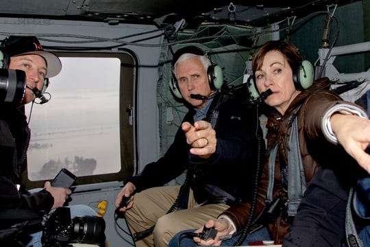 Vice President Mike Pence and Iowa Gov. Kim Reynolds, second right point to flooded areas, with Neb. Gov. Pete Ricketts, left, during a helicopter flight over areas affected by the flooding of the Missouri and Elkhorn Rivers, Tuesday, March 19, 2019, in Nebraska. Pence flew to Omaha, Neb., Tuesday to view damage and to offer support to first responders, volunteers and those displaced by the floods.