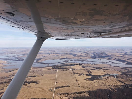 A small airplane flies over the swollen Missouri River on Monday, March 18, 2019, in western Iowa.