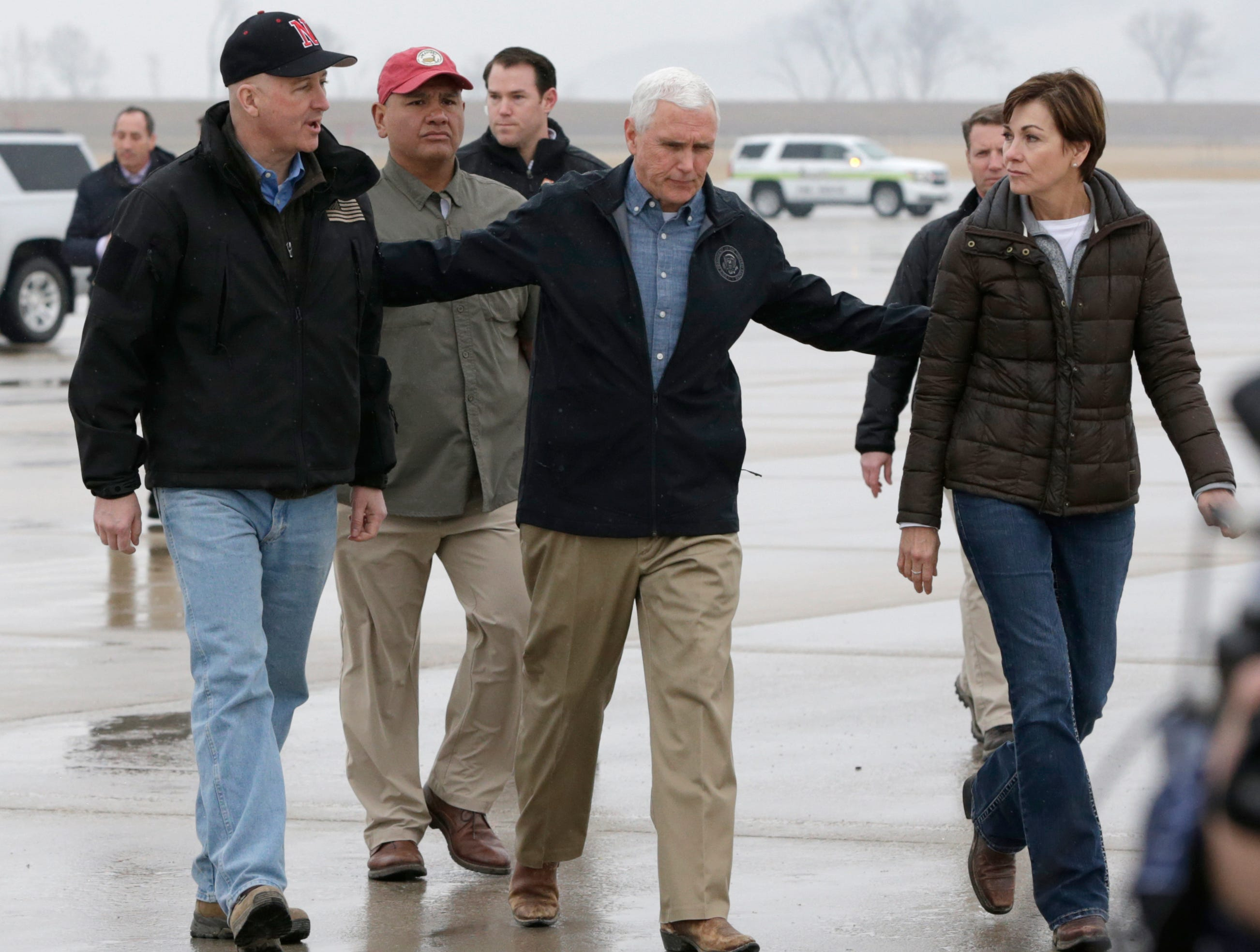 Vice President Mike Pence, center, is accompanied by Neb. Gov. Pete Ricketts, center, and Iowa Gov. Kim Reynolds upon his arrival in Omaha, Neb., Tuesday, March 19, 2019 to view the recent floods and offer support for it's victims.