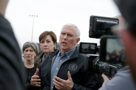 Vice President Mike Pence, center speaks to reporters upon arriving to Omaha, Neb., Tuesday, March 19, 2019, to view the extent of recent flooding and to offer support, with Sen. Joni Ernst, R-Iowa, left, Iowa Gov. Kim Reynolds, second left.