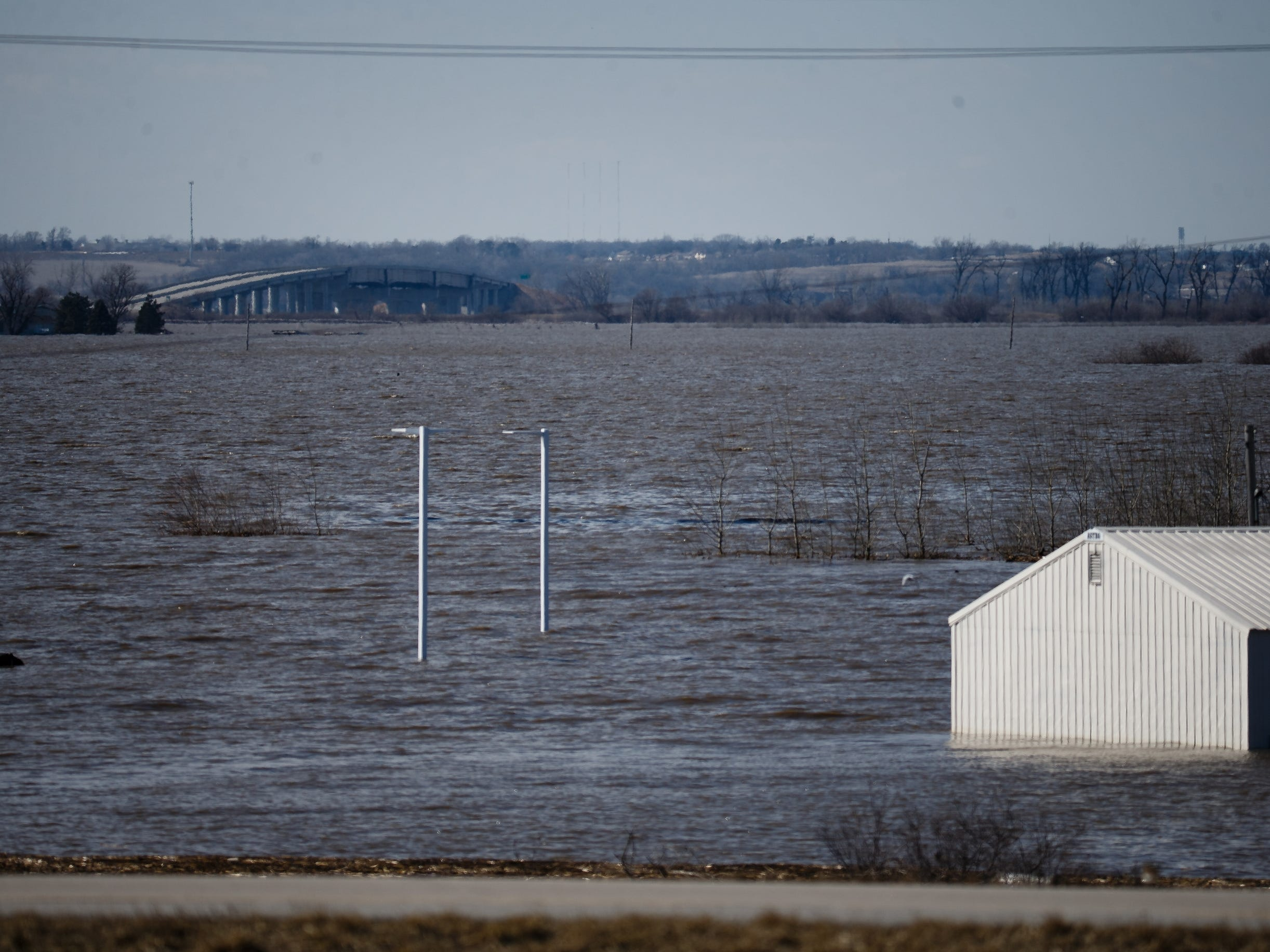 The bridge spanning the banks of the Missouri river is seen as flood waters continue to pour into the surrounding communities on Wednesday, March 20, 2019, in Mills County.