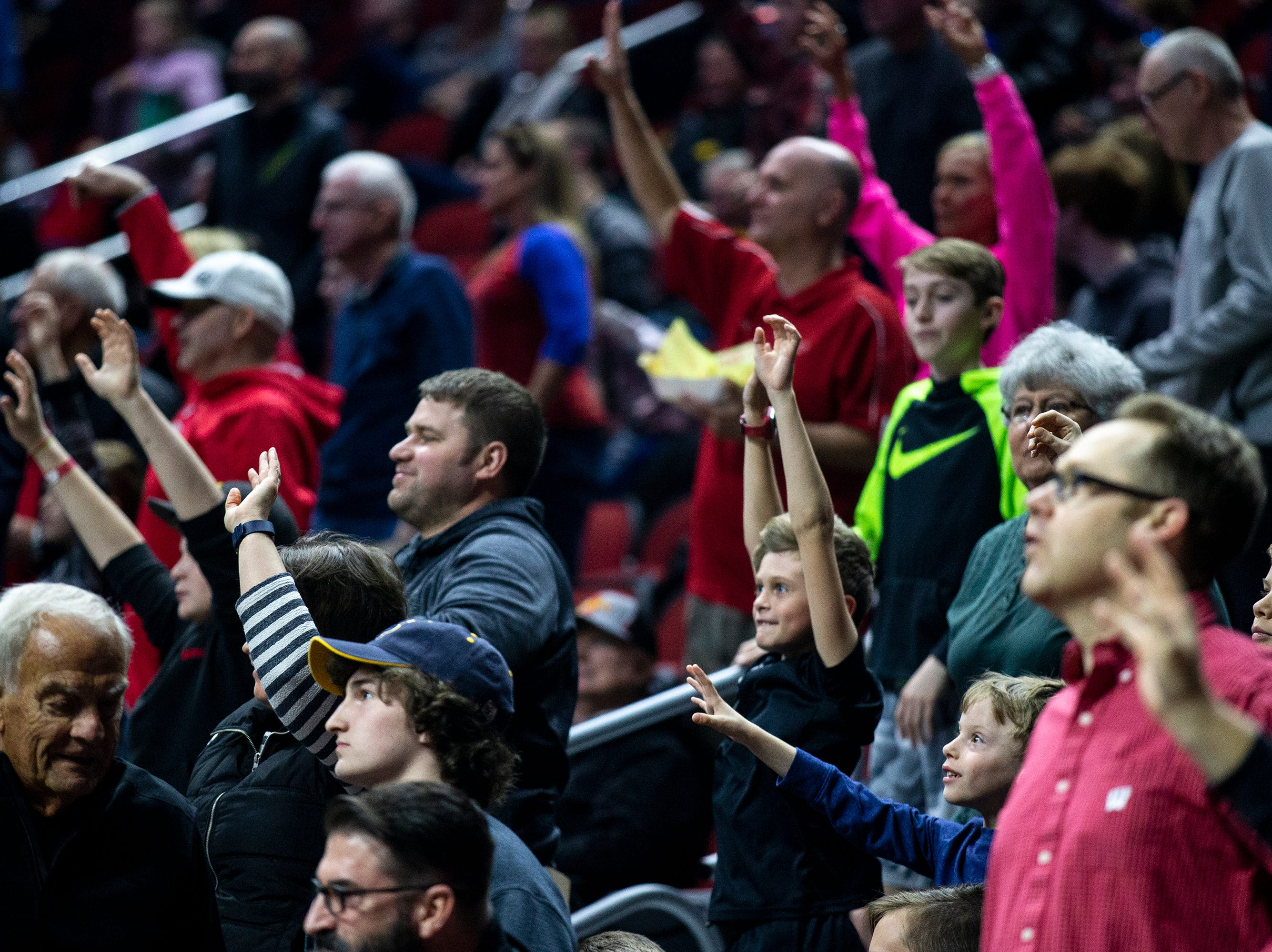 Fans put their hands in the air hoping to catch a t-shirt thrown into the stands during Minnesota's open practice before the first round of the NCAA Men's Basketball Tournament on Wednesday, March 20, 2019, at Wells Fargo Arena in Des Moines, Iowa. Minnesota will face Louisville in the first round on Thursday.