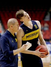 Michigan's Colin Castleton (11) leans over to hear coach John Beilein's instructions during practice at the NCAA college basketball tournament in Des Moines, Iowa, Wednesday, March 20, 2019. (AP Photo/Nati Harnik)