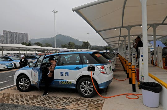 In this Monday, Jan. 7, 2019, photo, new electric-powered taxi are charged at a public charging station in Shenzhen city, south China's Guangdong province. One of China's major cities has reached an environmental milestone, an almost all electric-powered taxi fleet. The high-tech hub of Shenzhen in southern China announced at the start of this year that 99 percent of the 21,689 taxis operating in the city were electric.