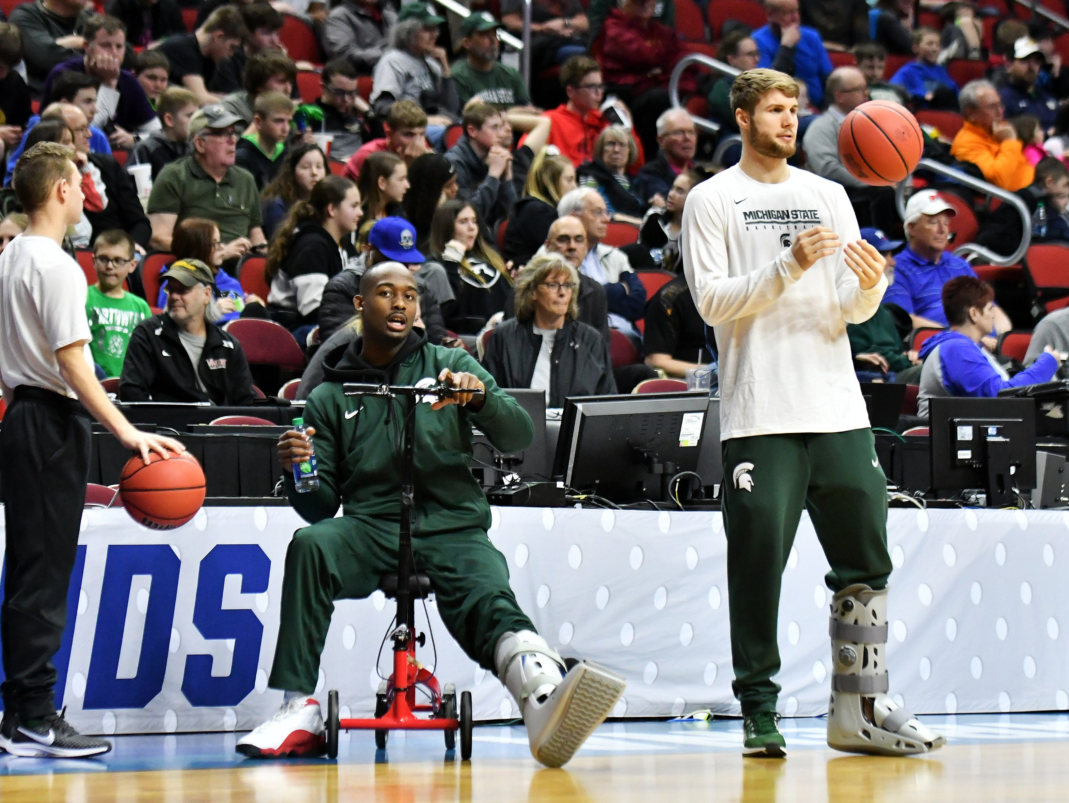 Two injured Spartans, Joshua Langford, left, and Kyle Ahrens, both wearing soft leg casts, watch their teammates practice.