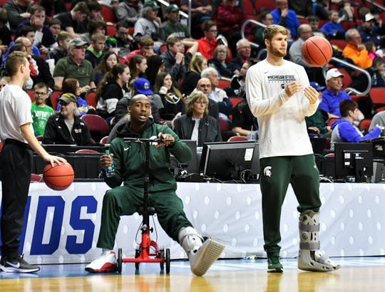 Two injured Spartans, Joshua Langford, left, and Kyle Ahrens, both wearing soft leg casts, watch their teammates practice Wednesday.