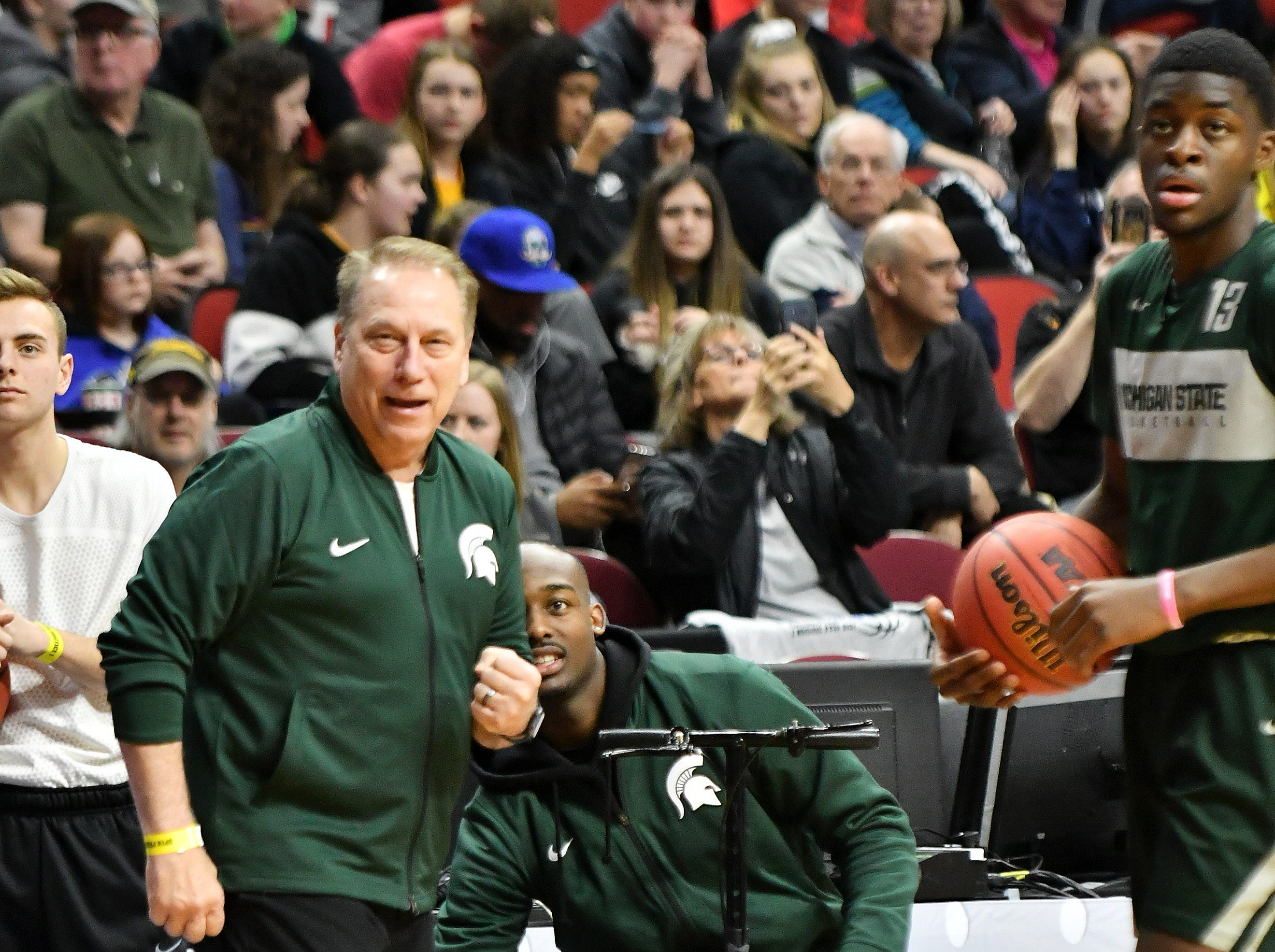 Michigan State head coach Tom Izzo watches a shot near injured Michigan State guard Joshua Langford on scooter at the Spartans' practice.