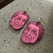 """A pair of earrings bearing the face of special counsel Robert Mueller. Carmen Martinez and Karen Walcott, owners of """"all of the things"""" have sold 500 Christmas ornaments and earrings with Mueller's face."""