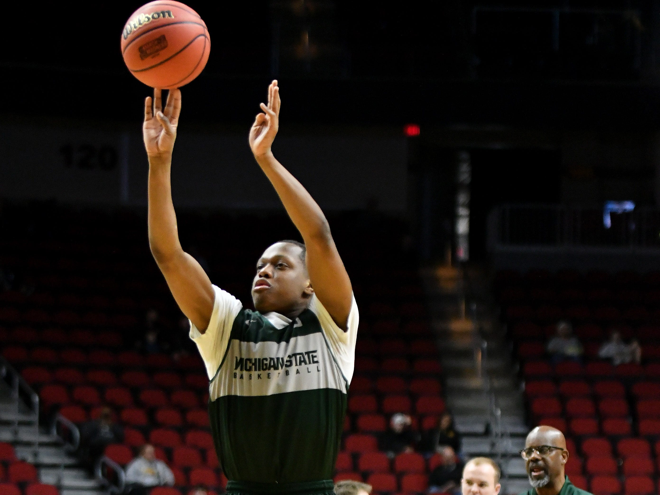 Michigan State guard Cassius Winston (5) takes a shot while assistant coach Mike Garland, right, watches.