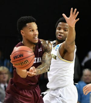 Montana guard Ahmaad Rorie (14) passes the ball around Michigan guard Zavier Simpson (3) in the second half of last year's first-round NCAA Tournament game.