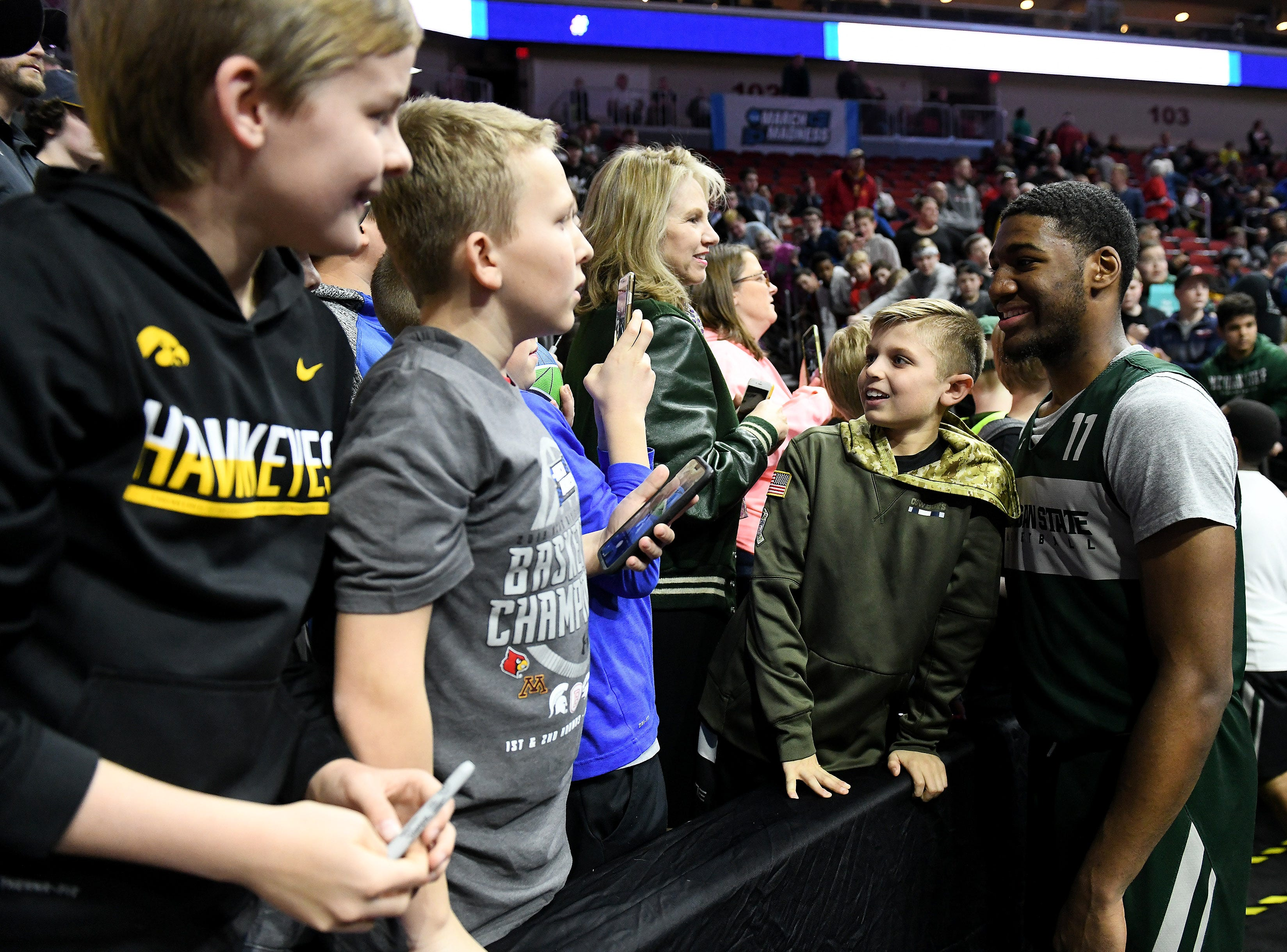 Michigan State forward Aaron Henry (11) stops to take a photo with Nash Kooken, 9, of Waukee, Iowa after at Wells Fargo Arena in Des Moines, Iowa Wednesday.
