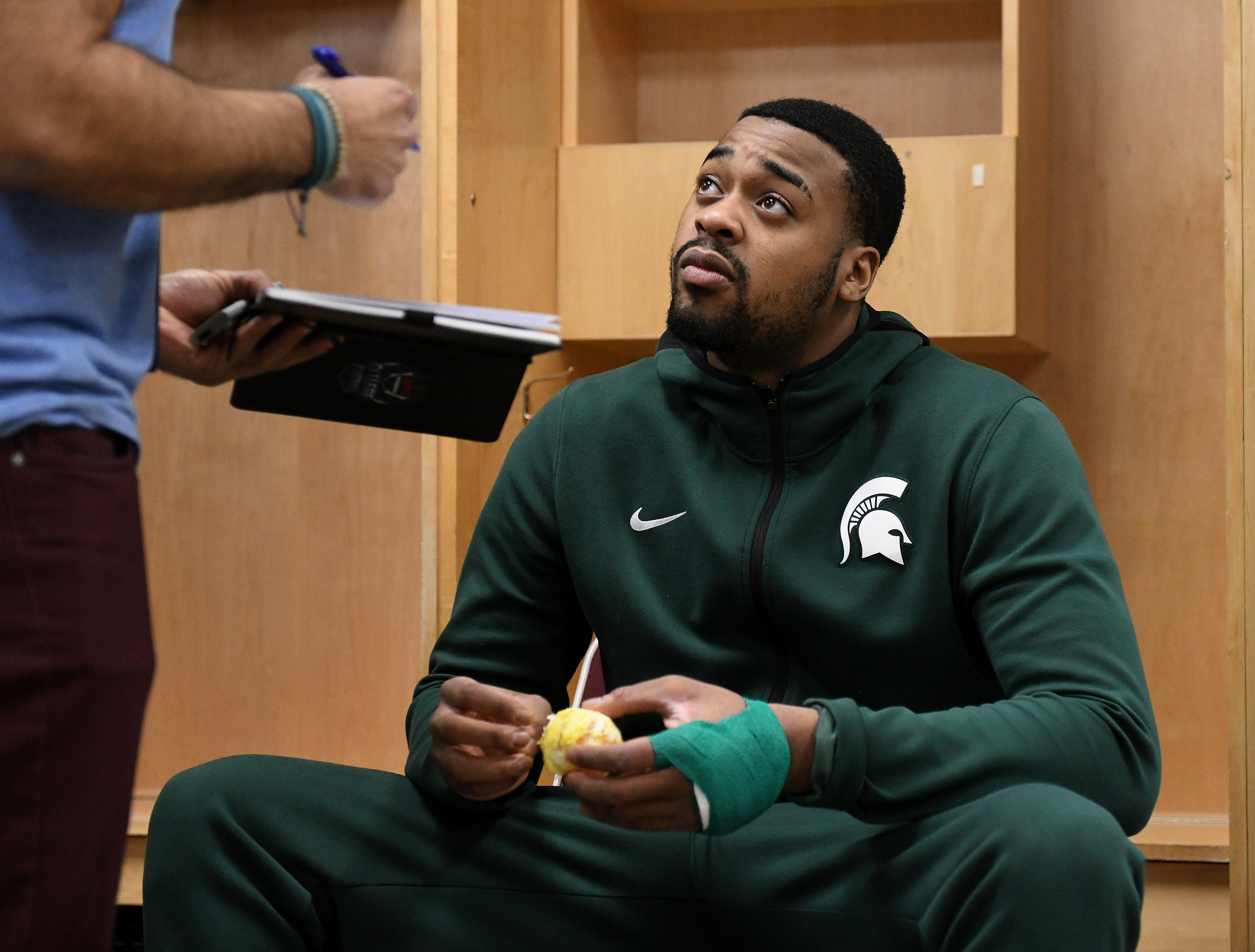 Michigan State forward Nick Ward talks with a reporter in the locker room before practice.
