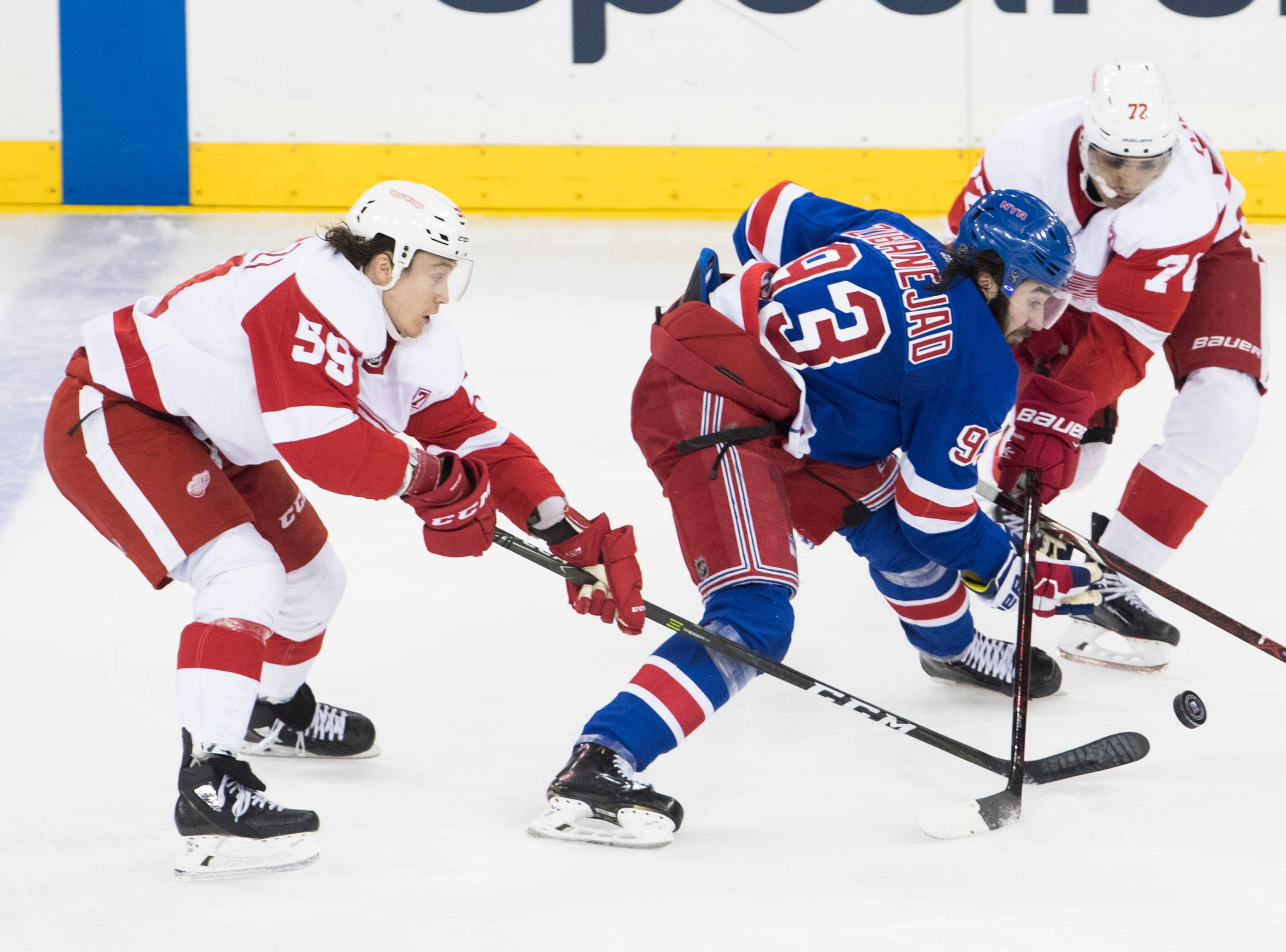 New York Rangers center Mika Zibanejad (93) skates against Detroit Red Wings left wing Tyler Bertuzzi (59) and center Andreas Athanasiou (72) during the third period.