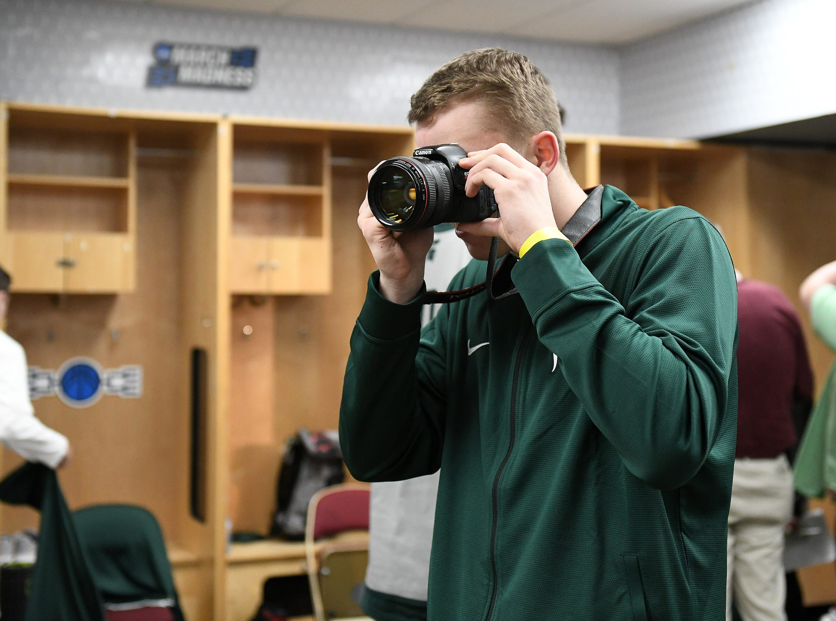 Michigan State forward Thomas Kithier takes photos with the team's social media photographer's camera during open locker room media availability Wednesday.