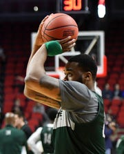Michigan State forward Nick Ward, wearing a protective brace on his left hand, takes a shot during practice