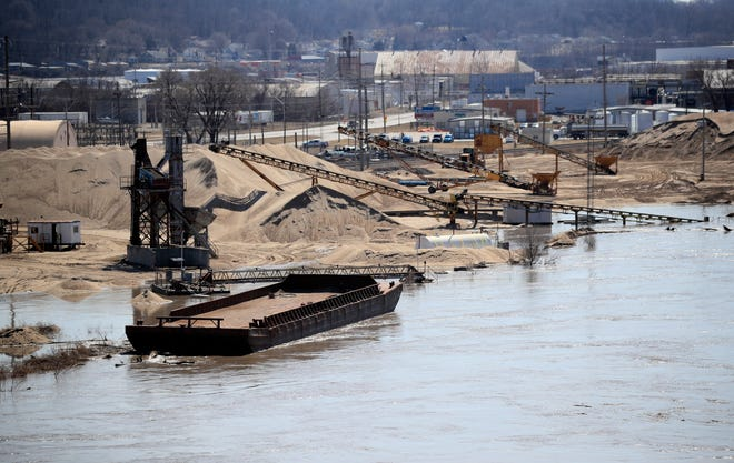 A barge is moored along the Missouri River as floodwaters begin to creep into a dredge operation in St Joseph, Mo., Monday, March 18, 2019.