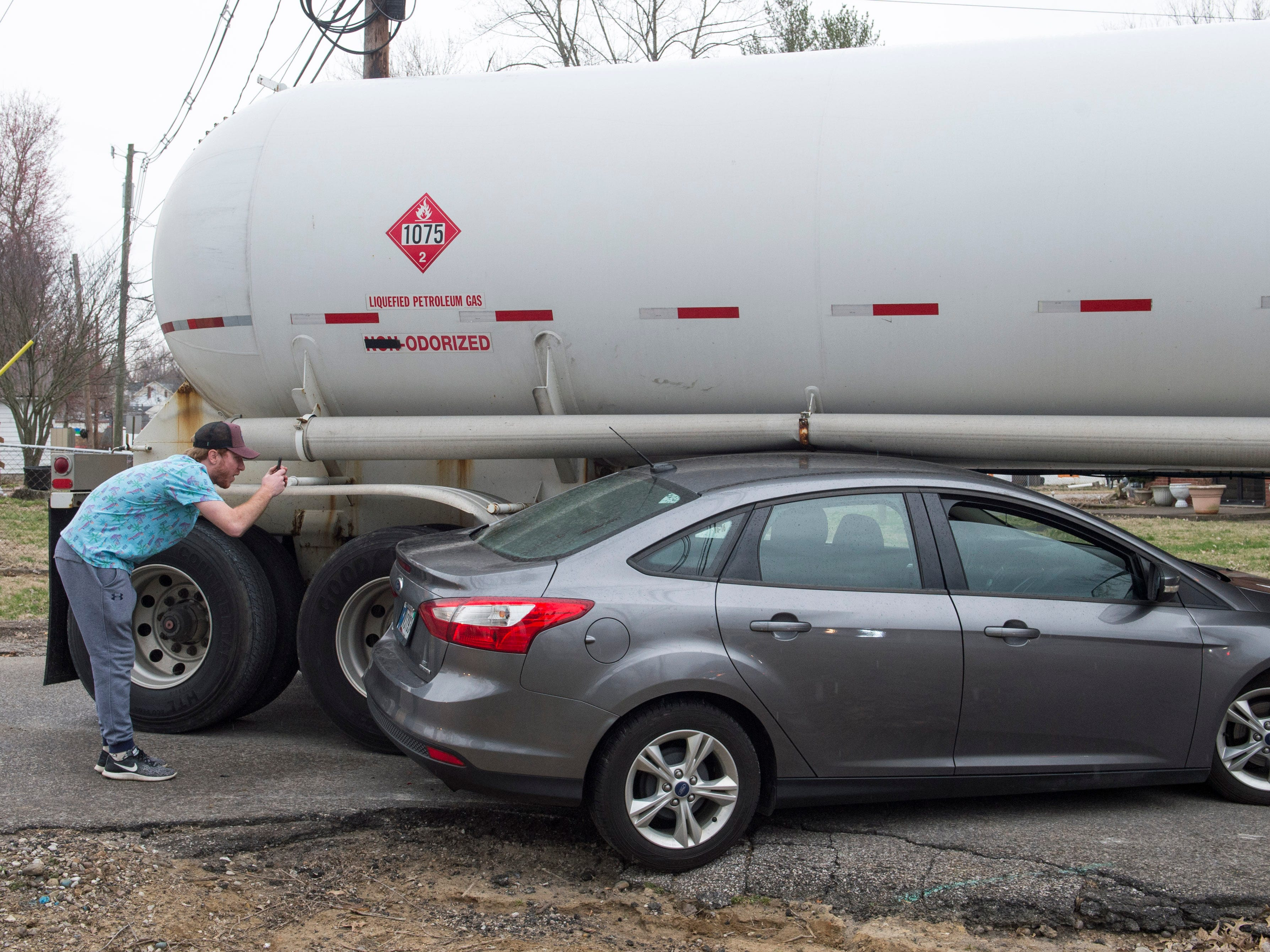The husband of the driver involved in an accident with a tanker truck at the intersection of Woods Ave. and Houge Rd. takes photos of the damage Wednesday, March 20, 2019. The truck was empty and no one was injured.