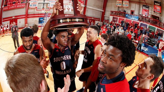 Kobe Caldwell holds the Midwest Regional championship trophy alongside his teammates.