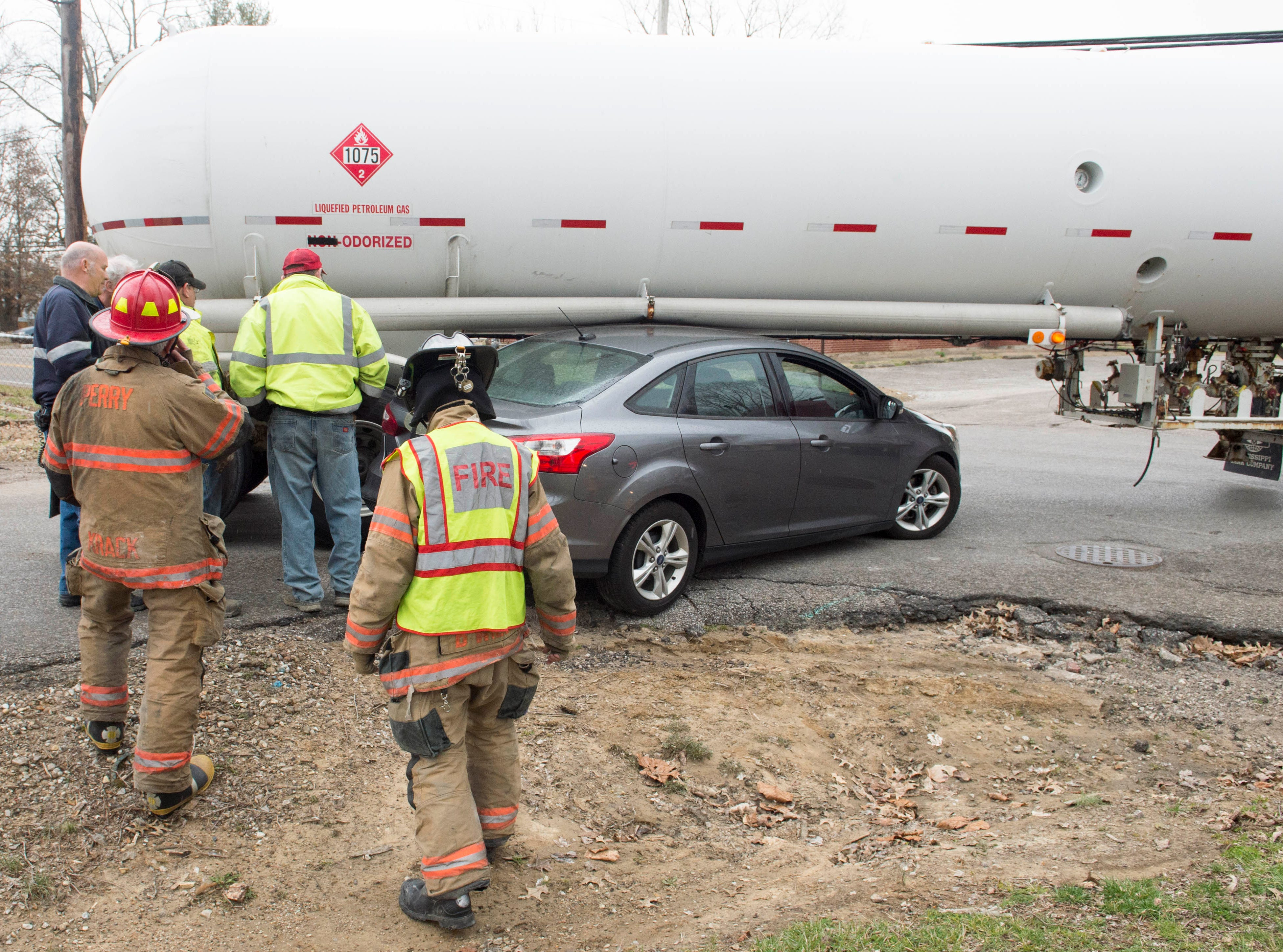 Emergency responders mull over options on how to remove a vehicle from under a tank truck at the intersection of Woods Ave. and Houge Rd. on Evansville's West Side on Wednesday, March 20, 2019. The truck was empty and no one was injured.