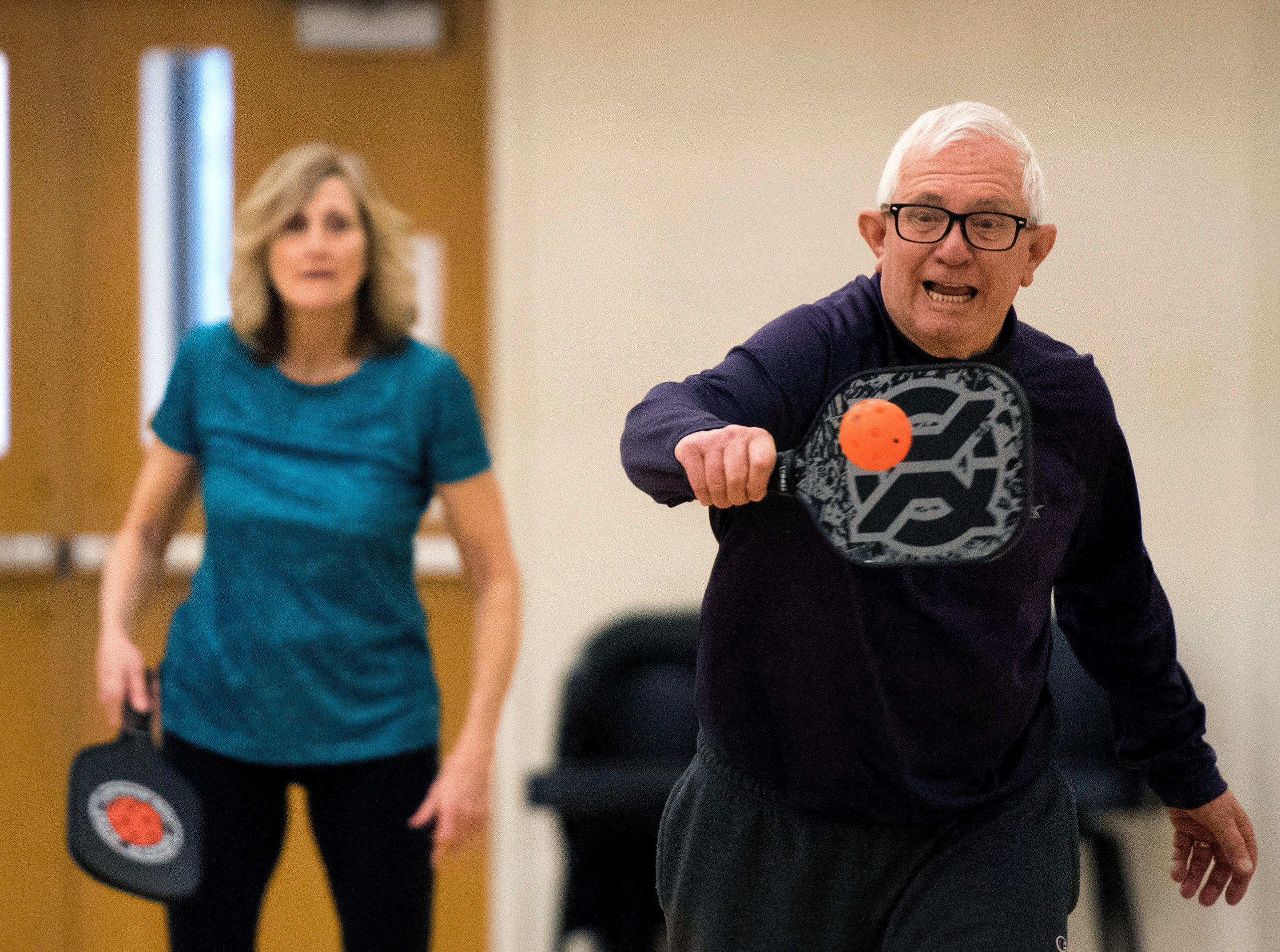 James Brown, front, returns the ball while playing a game of pickle ball with partner Jean Schmitt, back, at St. Peter's Methodist Church Wednesday, March 20, 2019.