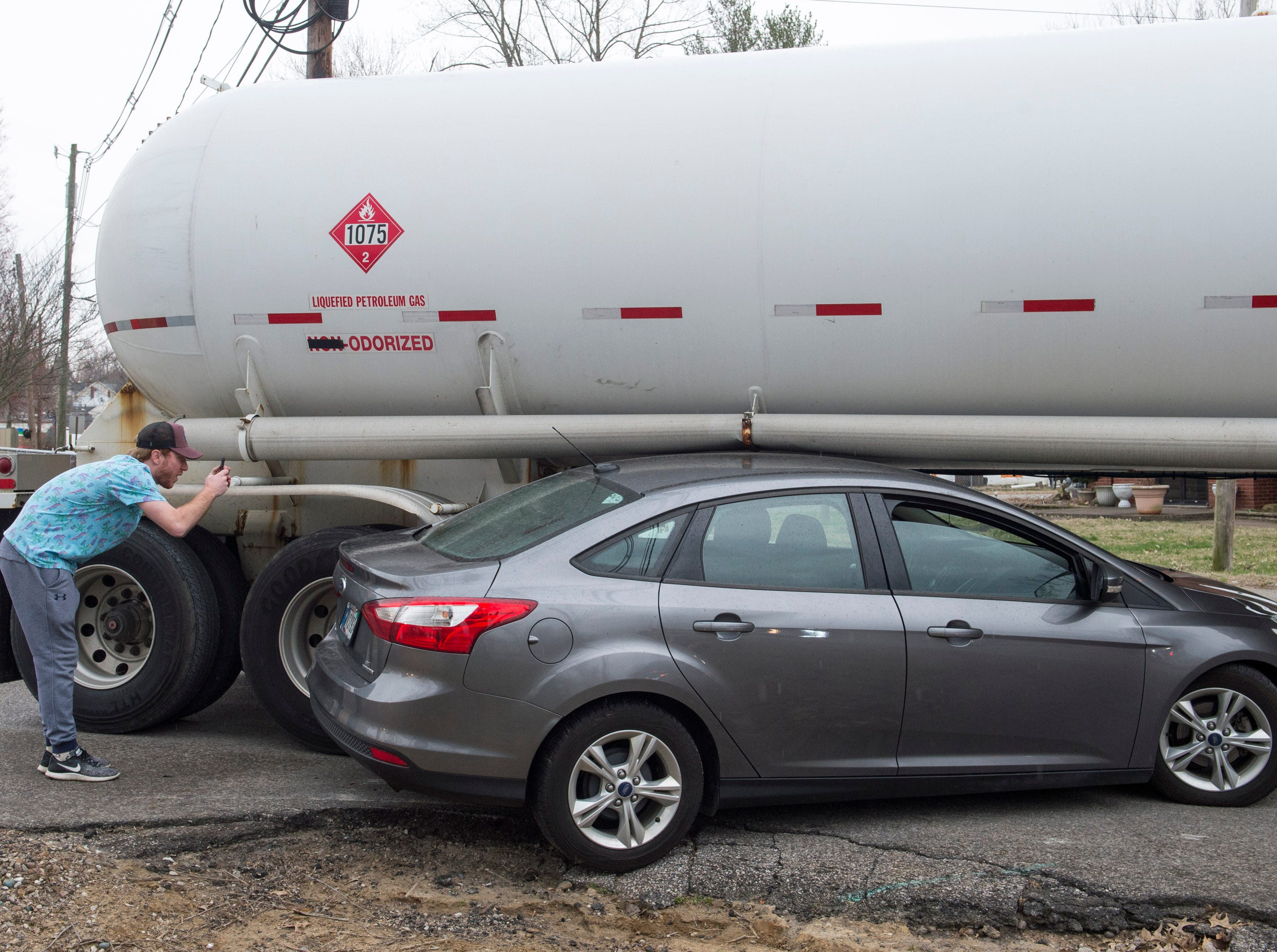 The husband of the driver involved in an accident with tanker truck at the intersection of Woods Ave. and Houge Rd. on Evansville's West Side takes photos of the damage Wednesday, March 20, 2019. The truck was empty and no one was injured.