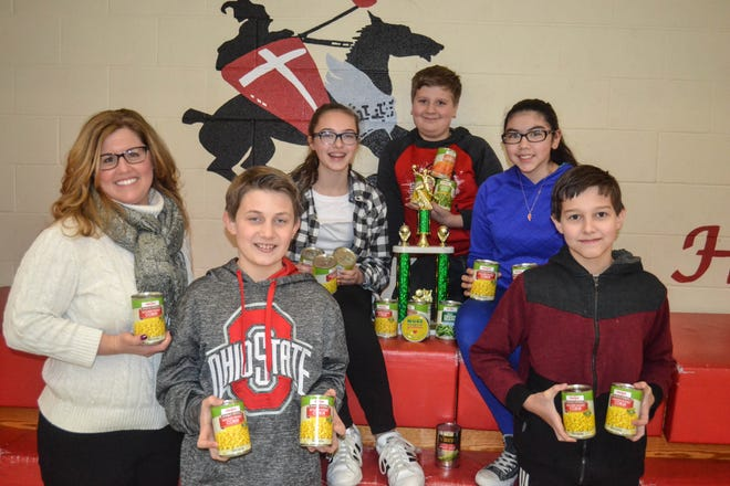 Solomon Lutheran School Principal Natalie Schiets  and some of her basketball players pose with a few of the cans they brought to the Napoleon Basketball Tournament. Shown with her are, back, left to right: Carys Ruck, Tristan Rodriguez and Natalie Segovia. In front are, left to right: Mitchell Gillig and Jack Morris.