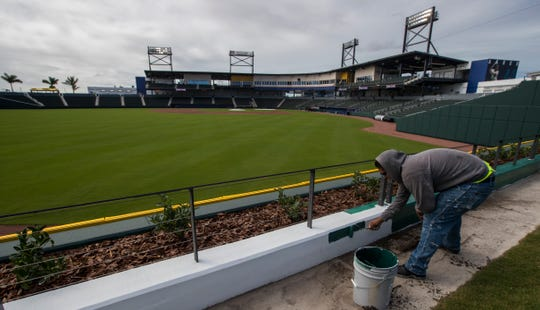 Carlos Orozco, an employee for Sourini Painting, puts some of the finishing touches on one of the railings at CoolToday Park in North Port, Wednesday, March 20, 2019. The facility will be the new spring training home of the Atlanta Braves.