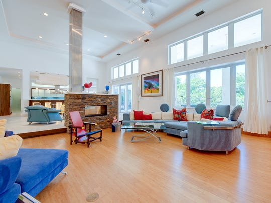 The sunken family room has bamboo floors. A fireplace separates it from the living room above.