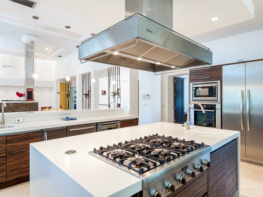The kitchen has an island with ports that pop up and electrical outlets that are imbedded.