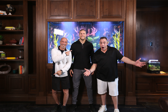 "Brett Raymer, left, and Wayde King, right, hosts of Animal Planet show ""Tanked,"" reveal the custom eel tank they built for Green Bay Packers linebacker Clay Matthews in his home."