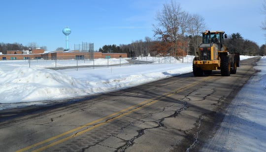 A city of Oconto loader passess Oconto Elementary School on Doran Avenue in early March. The road will be reconstructed this summer, which should provide more safety for students and others, city officials say.