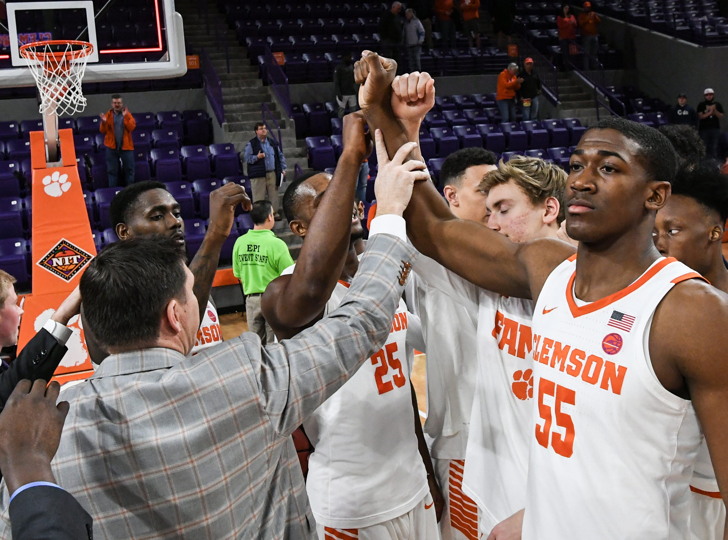 Clemson head coach Brad Brownell joins his team celebrating after a 75-69 win in the NIT at Littlejohn Coliseum in Clemson Tuesday, March 19, 2019.