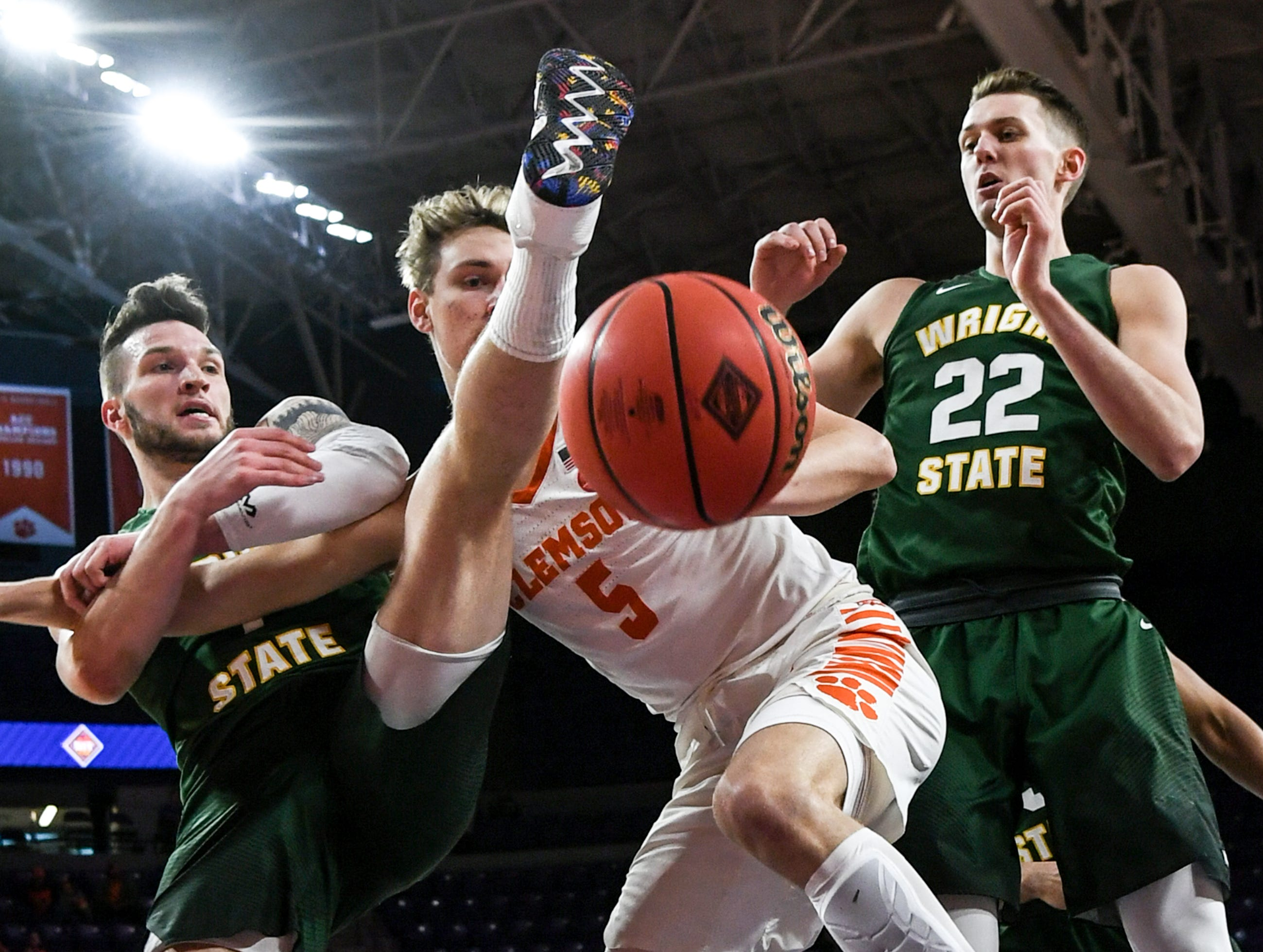 Clemson forward Hunter Tyson(5), middle, watches a loose ball with Wright State forward Bill Wampler(1), left, and Wright State center Parker Ernsthausen(22), right, during the first half of the NIT at Littlejohn Coliseum in Clemson Tuesday, March 19, 2019.