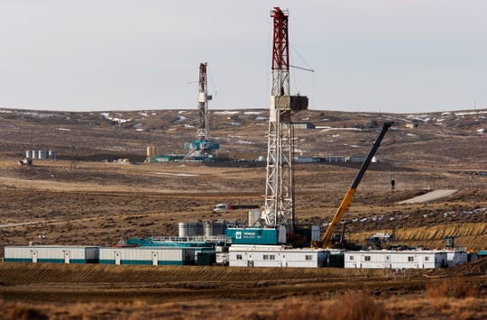 FILE- In this March 5, 2013, file photo, Trinidad Drilling rigs are seen off of Way Highway 59 outside of Douglas, Wyo. A judge has blocked oil and gas drilling on almost 500 square miles in Wyoming and says the government must consider cumulative climate change impacts of leasing public lands across the U.S. for energy development. The order marks the latest in a string of court rulings over the past decade faulting the government's consideration of emissions when issuing energy leases. (Leah Millis/The Casper Star-Tribune via AP, File)