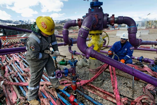 FILE - In this March 29, 2013, file photo, workers tend to a well head during a hydraulic fracturing operation outside Rifle, in western Colorado. A judge has blocked oil and gas drilling on almost 500 square miles in Wyoming and says the government must consider cumulative climate change impacts of leasing public lands across the U.S. for energy development. The order marks the latest in a string of court rulings over the past decade faulting the government's consideration of emissions when issuing energy leases. (AP Photo/Brennan Linsley, File)