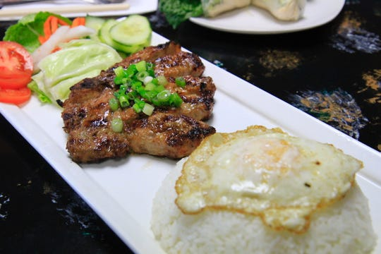 The pork chop with eggs comes in three sections: fresh vegetables, a tender pork chop rice topped with an egg.