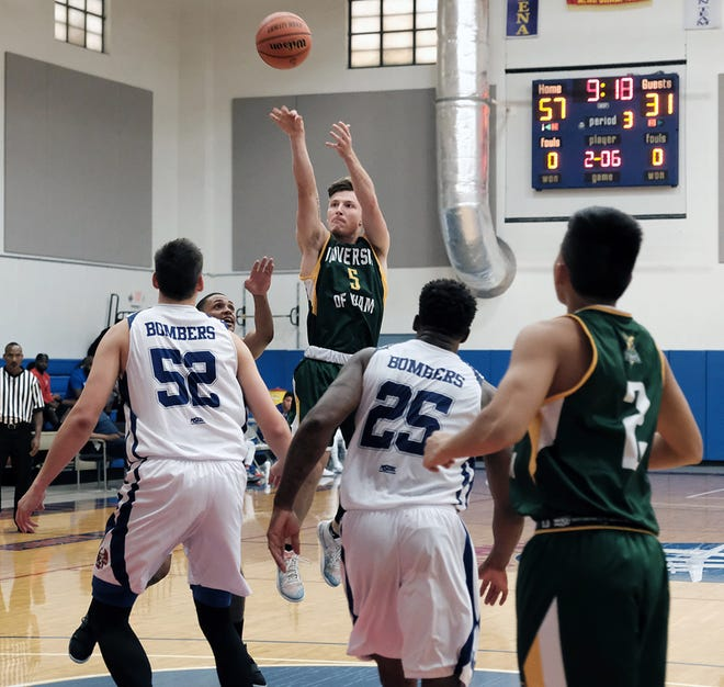 UOG's Logan Hopkins shoots over a couple of Bombers. Hopkins scored 40 but the Tritons lost to the Andersen Bombers 125-85.
