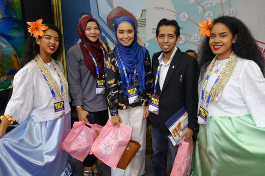 Malaysian fairgoers with Guma Taotao Tano dancers Vivian Amon and Malaysian Association of Tour and Travel Agents Fair.