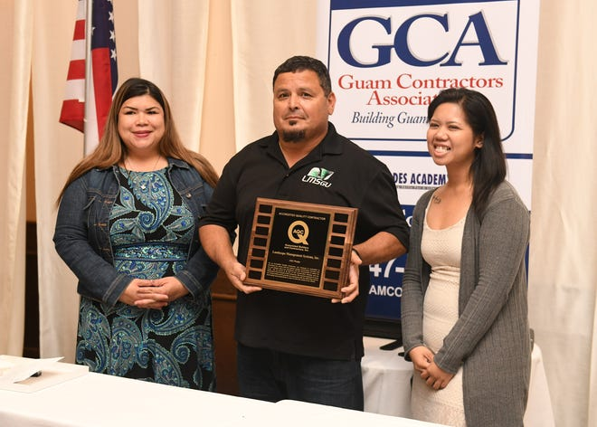 In this March 20, 2019, file photo, Ruben Montalvo, center, Landscape Management Systems Guam quality control mananger, is flanked by Guam Contractors Association Vice Chairperson Jessica Barrett, left, and Melanie Paglingayen, LMS Guam human resource manager, after receiving an award at a GCA luncheon at the Hyatt Regency Guam.
